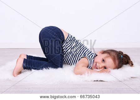 Beautiful small girl lying on floor on wall background