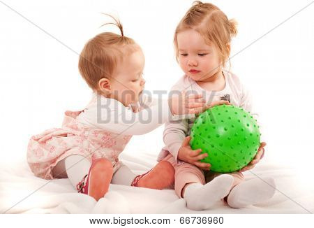 Two small girls playing with ball