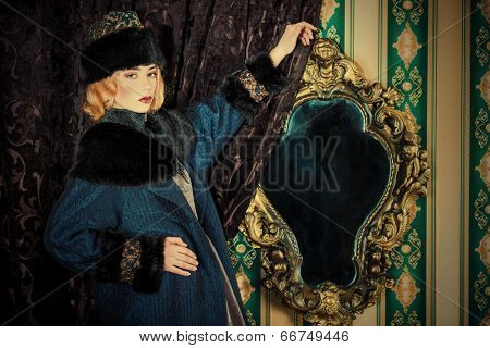 Gorgeous fashion model in a rich historical costume. Fur clothing. Vintage. Luxury style.