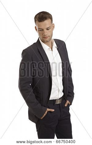 Young businessman standing with hands in pockets, looking down.