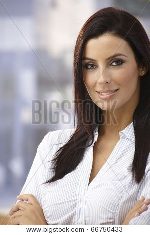 Outdoor portrait of confident young woman smiling arms crossed.