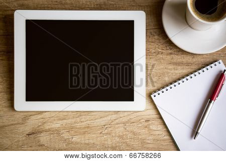 Tablet with notebook on wooden table, top view