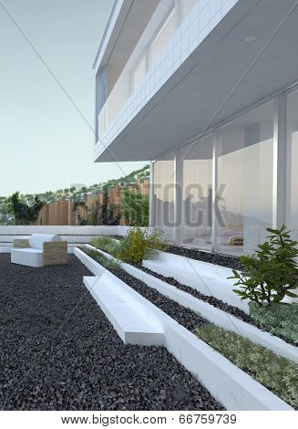 Pebble patio with a comfortable armchair in front of a modern house with large glass windows and a jutting upper storey