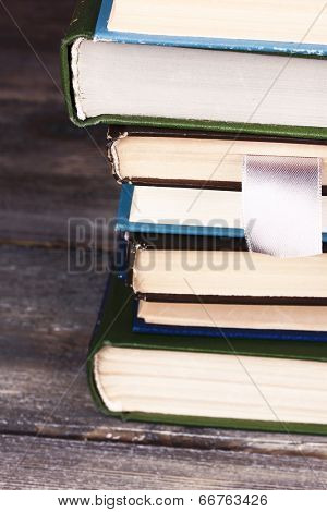 Stack of colorful hardback and paperback books, close-up, on wooden background