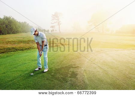 Golfer chipping onto the green at sunrise on the golf course in misty conditions