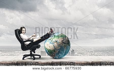 Young businesswoman sitting in chair and reading book. Elements of this image are furnished by NASA