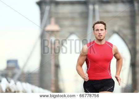 Running man sprinting in New York City. Runner on training run outside. Caucasian male runner and fitness sport model in sprint wearing compression clothing on Brooklyn Bridge, New York City, USA.