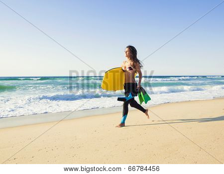 A beautiful girl running at the beach with her bodyboard