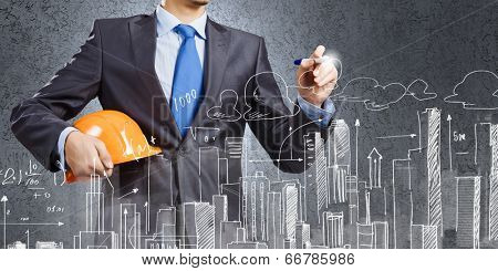 Young man engineer drawing sketches of construction project