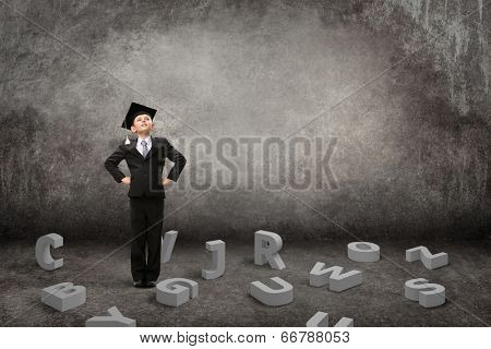 Full-length portrait of little student with hands on hips and letters under his feet on grey background. Concept of study and graduation