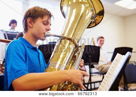 Male Pupil Playing Tuba In High School Orchestra