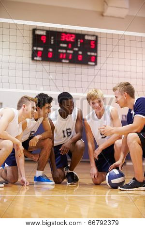 Male High School Volleyball Team Having Team Talk From Coach