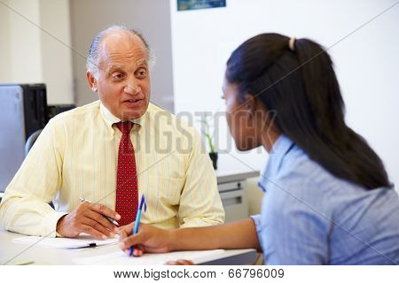 Female Student Talking To High School Counselor