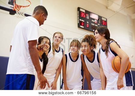 High School Basketball Team Having Team Talk With Coach