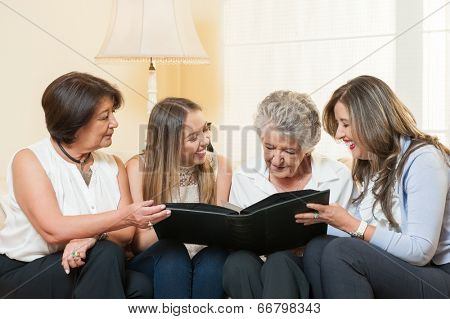 Women watching family album at home
