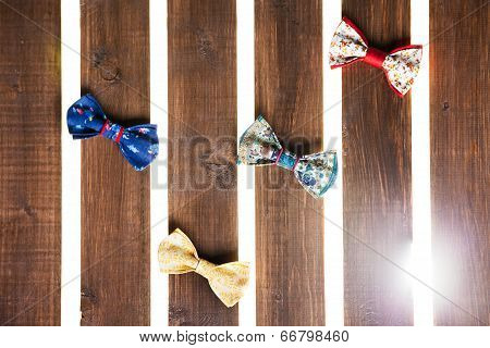 Set of handmade bow tie over wooden background