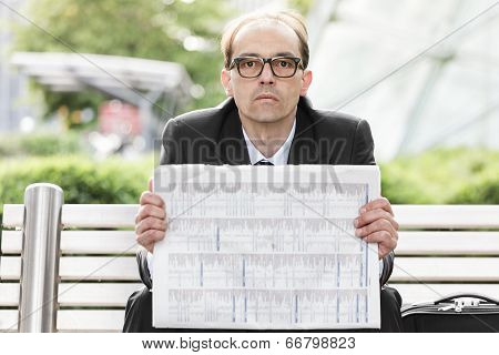 Sad Businessman With Newspaper In His Hands