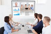 stock photo of video chat  - Business team attending video conference at desk in office - JPG