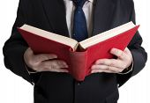 stock photo of glossary  - man holding an open red book closeup on a white - JPG