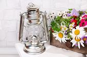 picture of kerosene lamp  - Beautiful flowers in crate with kerosene lamp on wooden stand on light background - JPG