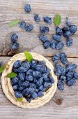 stock photo of honeysuckle  - Fresh Ripe Honeysuckle Berries in Wicker Bowl on Rustic Wooden background - JPG