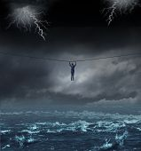 picture of survival  - Surviving the storm business concept with a businessman hanging on to a tightrope crossing over dangerous water as a concept and metaphor for conquering adversity and overcoming challenges - JPG