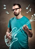 stock photo of rockabilly  - Man with glasses and beard playing imaginary air guitar - JPG
