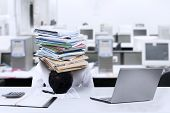 picture of overwhelming  - Depressed young businessman with a pile of documents on his head at office - JPG