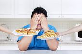 stock photo of reject  - Fat man rejecting to eat junk food - JPG