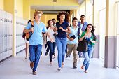 stock photo of 16 year old  - Group Of High School Students Running In Corridor - JPG