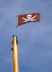 picture of skull crossbones flag  - Jolly Roger skull and crossbones pirate flag upon a wood mast  - JPG