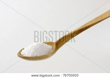 whit of coarse grained salt on the old wooden spoon