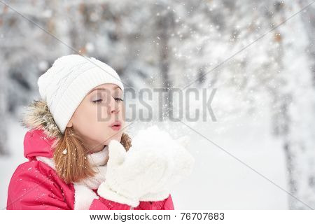 Happy Girl On A Frosty Winter Walk On Street Blows Snow From Hands