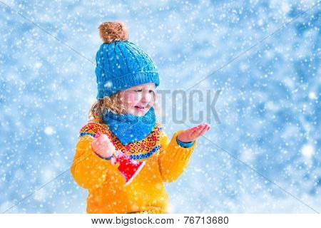 Cute Little Girl Catching Snow Flakes
