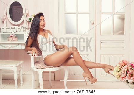 A sexy mulatto woman lying on the bed in a pink room