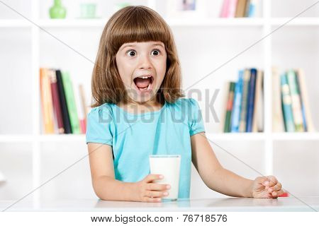 Little girl with glass of milk making a face