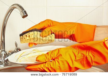 Hands in gloves with dirty plate over the sink in kitchen