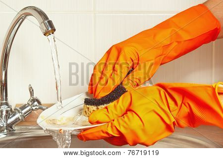 Hands in gloves wash the dishes under running water in kitchen