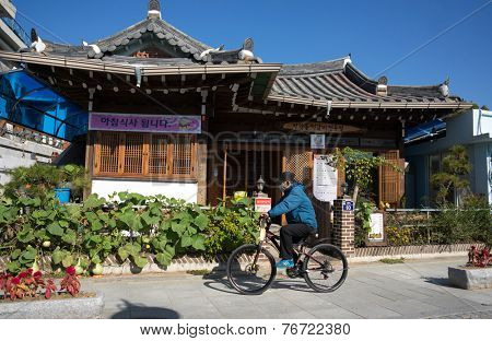 JEONJU, SOUTH KOREA - 03 NOVEMBER 2014: An unidentified cyclist cycles past old traditional Korean houses in this vintage town. The Korean Hanok Village in Jeonju is a major tourist attraction.