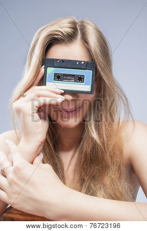 Young Caucasian Blond Woman Holding Audio Cassette In Front