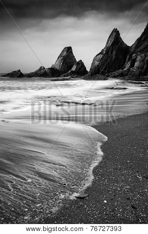 Landscape Seascape Of Jagged And Rugged Rocks On Coastline With Long Exposure Motion Blur  Black And