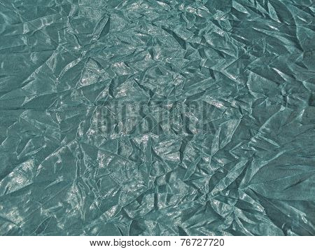 Texture Of Shiny Fabric With Creased Folds In Turquoise Color