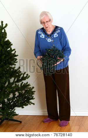 senior trying to untangle christmas lights