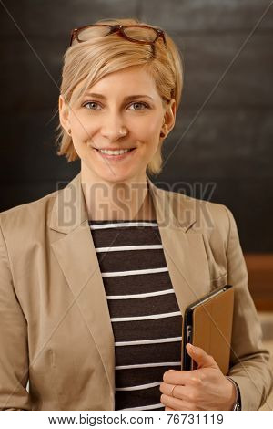 Closeup portrait of smiling young businesswoman looking at camera, holding folder in hand.