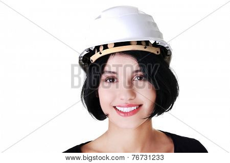 Portrait of a woman with hardhat looking at camera.