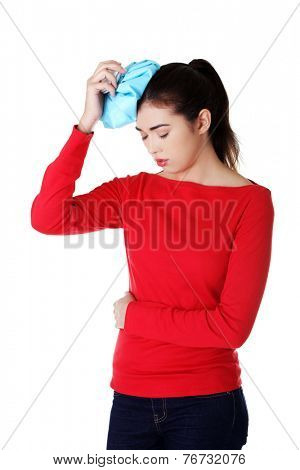 Woman with headache touching head by icebag.
