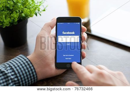 Man Holding Iphone 6 With Facebook On The Screen
