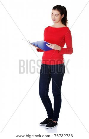 Pretty female student reading her notes.