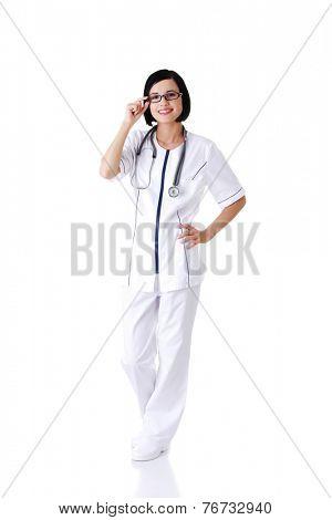 Full length female doctor touching her eyewear.