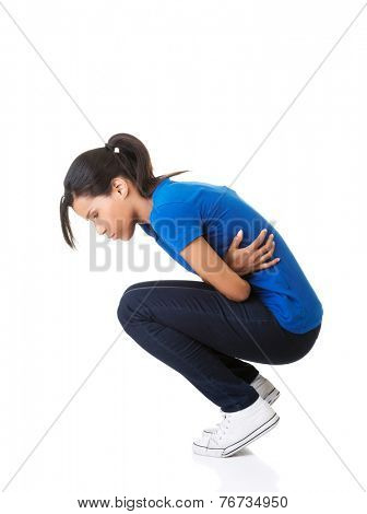 Side view of young woman with stomachache kneeling